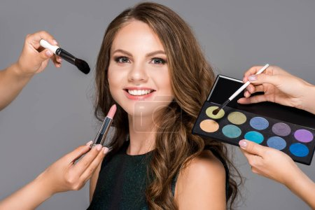 partial view of makeup artists with cosmetics and beautiful smiling woman isolated on grey