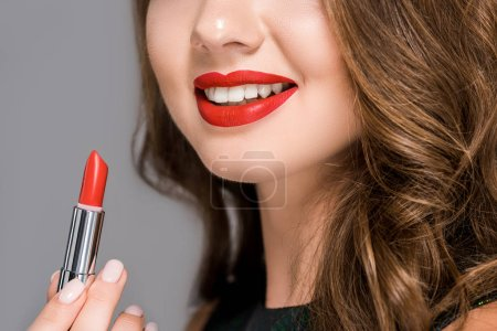 Photo pour Vue partielle de femme souriante avec rouge à lèvres rouge isolé sur fond gris - image libre de droit