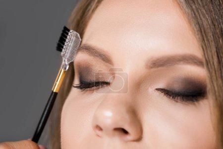 vue partielle de la maquilleuse avec pinceau pour sourcils et le modèle avec les yeux fermés isolés sur gris