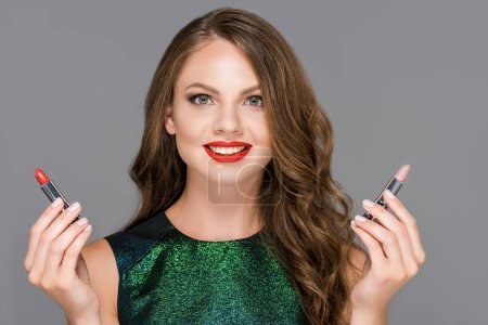 portrait of beautiful smiling woman showing lipsticks in hands isolated on grey
