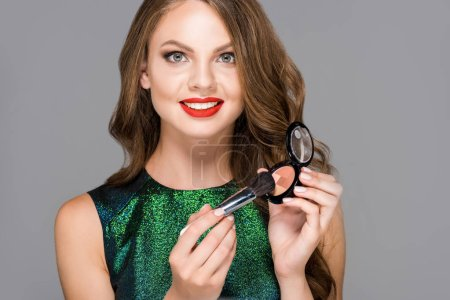 portrait of attractive smiling woman with makeup brush and blush isolated on grey