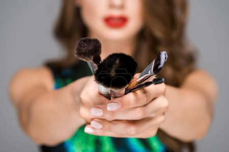 partial view of woman showing makeup brushes in hands on grey background