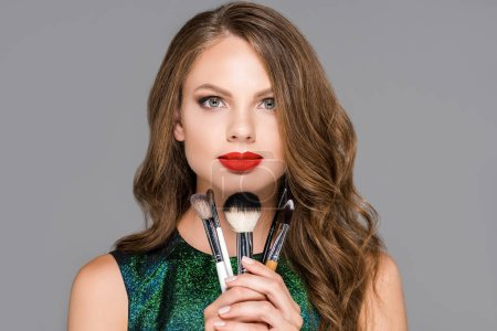 portrait of beautiful woman with makeup brushes looking at camera isolated on grey