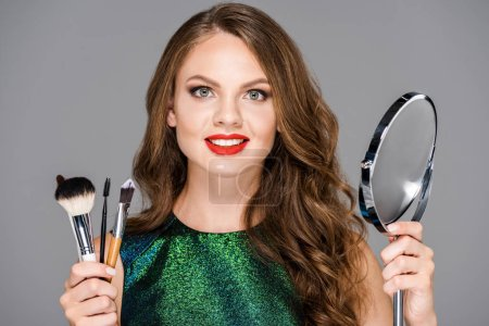 portrait of beautiful smiling woman with makeup brushes and mirror isolated on grey