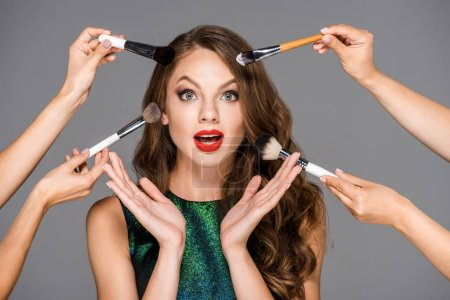 cropped shot of makeup artists with makeup brushes and shocked woman isolated on grey