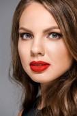 Portrait de jeune femme attirante avec rouge à lèvres sur les lèvres en regardant la caméra