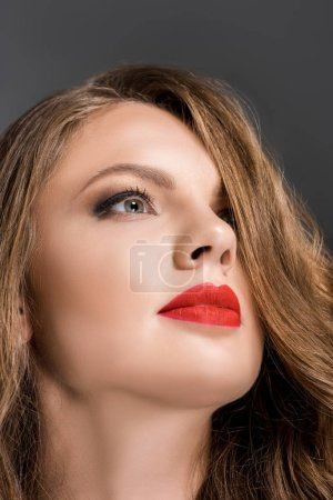 portrait of beautiful woman with red lipstick on lips looking away isolated on grey