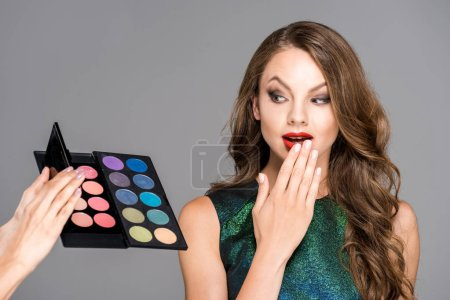 partial view of makeup artist showing eyeshadows palette to shocked model isolated on grey