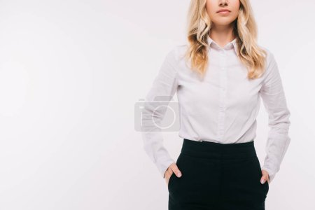 cropped image of businesswoman standing with hands in pockets isolated on white