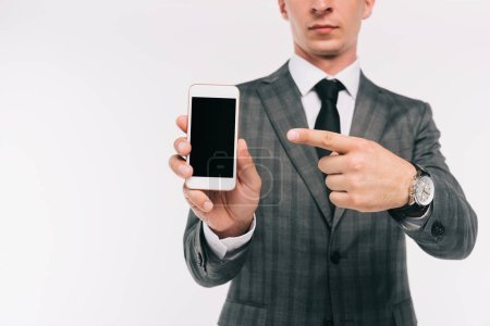 cropped image of businessman pointing on smartphone with blank screen isolated on white