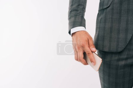 cropped image of businessman putting smartphone into pocket isolated on white