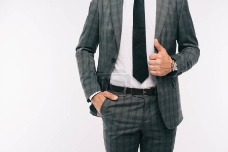 cropped image of businessman holding jacket and standing with hand in pocket isolated on white