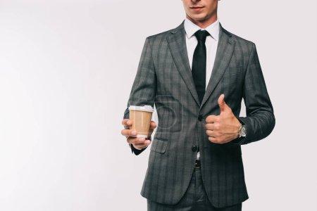 Photo pour Image recadrée de l'homme d'affaires tenant du café dans une tasse en papier et montrant pouce vers le haut isolé sur blanc - image libre de droit