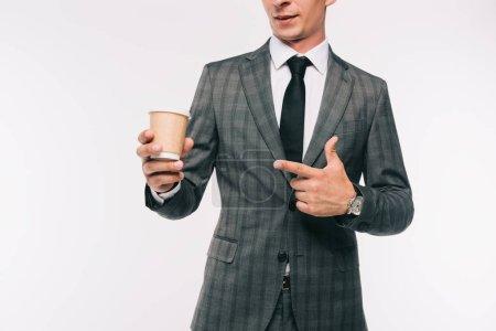 Photo pour Image recadrée de l'homme d'affaires pointant sur le café dans une tasse en papier isolé sur blanc - image libre de droit