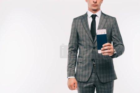 Photo pour Image recadrée d'homme d'affaires détenant passeport et billet isolé sur blanc - image libre de droit