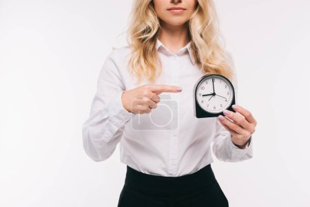 cropped image of businesswoman pointing on clock isolated on white