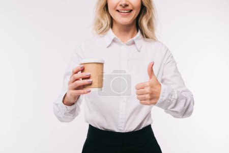 cropped image of businesswoman holding disposable coffee cup and showing thumb up isolated on white