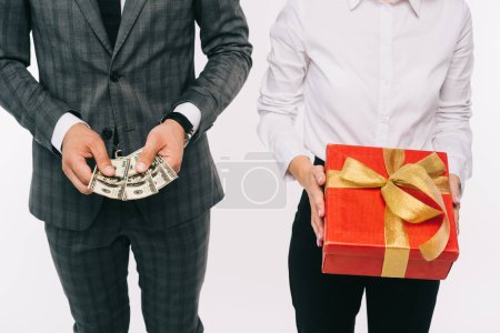 Photo for Cropped image of businesspeople holding dollars and gift box isolated on white - Royalty Free Image