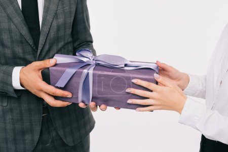 cropped image of businesswoman presenting gift to coworker isolated on white