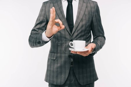 cropped image of businessman holding cup of coffee and showing okay gesture isolated on white
