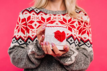 cropped image of girl in sweater holding cup with heart sign isolated on pink