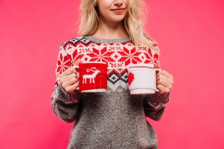 cropped image of girl in sweater holding two different cups isolated on pink