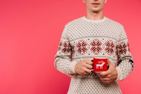 cropped image of man in sweater holding cup with deer silhouette isolated on pink