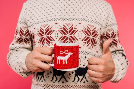cropped image of man in sweater holding cup with deer silhouette and showing thumb up isolated on pink
