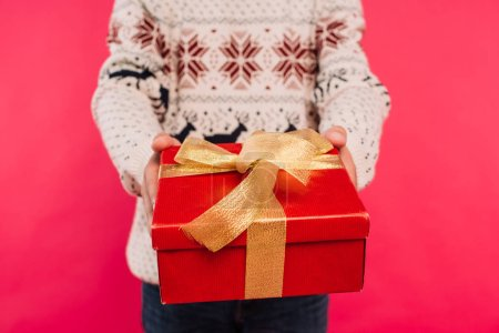 cropped image of man in sweater showing gift box isolated on pink