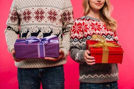 Foto de Imagen recortada de pareja en suéteres con regalos aislados en rosa - Imagen libre de derechos