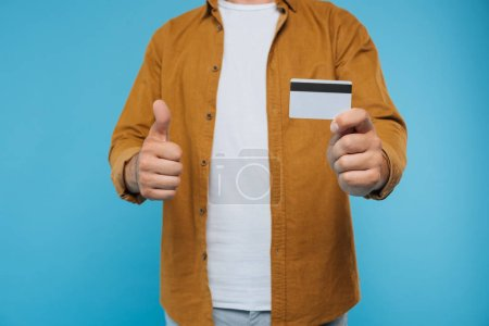 cropped image of man showing thumb up and holding credit card isolated on blue