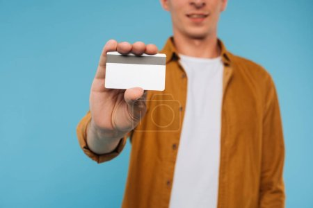 cropped image of man showing credit card isolated on blue