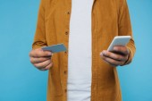 cropped image of man holding credit card and smartphone isolated on blue