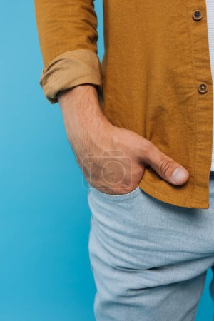 cropped image of man standing with hand in pocket isolated on blue