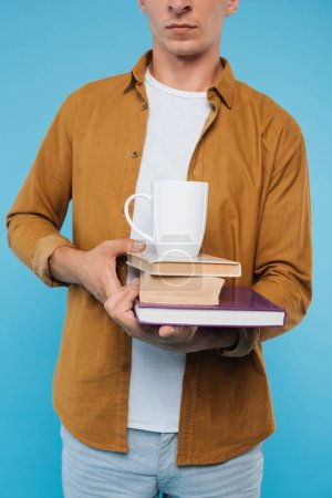 cropped image of man holding books and cup of coffee isolated on blue