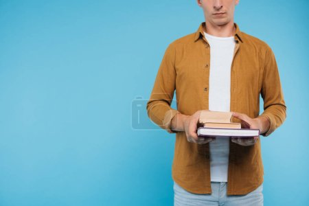 Photo for Cropped image of man holding three books isolated on blue - Royalty Free Image
