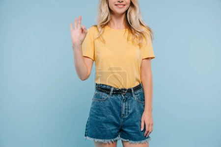 Photo for Cropped image of girl in shirt and shorts showing okay gesture isolated on blue - Royalty Free Image