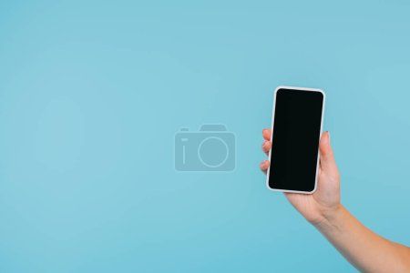 cropped image of girl holding smartphone with blank screen in hand isolated on blue