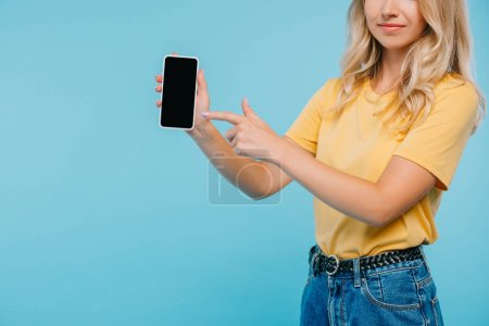 cropped image of girl in shirt and shorts pointing on smartphone isolated on blue