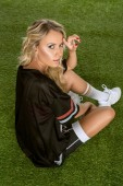 sporty young woman in american football uniform sitting on grass and looking at camera