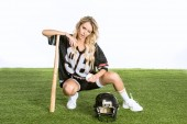 athletic young woman in american football uniform with helmet and baseball bat sitting on grass isolated on white