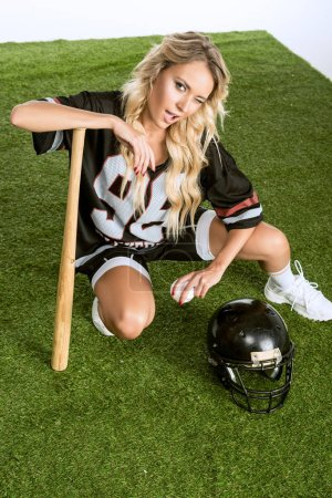 high angle view of athletic young woman in american football uniform with helmet and baseball bat sitting on grass