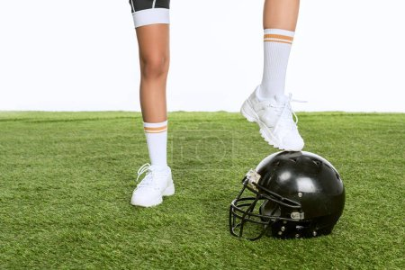 cropped shot of woman standing on american football helmet on green grass isolated on white
