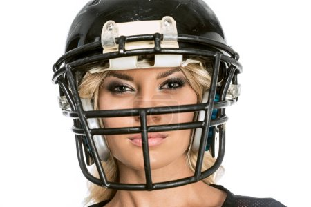 close-up shot of serious young woman in american football helmet looking at camera isolated on white