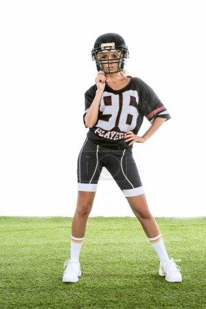 Photo pour Jeune femme athlétique permanent uniforme de football américain sur l'herbe verte isolé sur blanc - image libre de droit