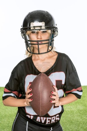 sporty young woman in american football uniform with ball looking at camera isolated on white