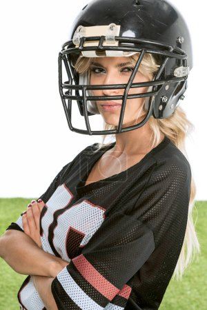 serious young woman in american football uniform looking at camera with crossed arms isolated on white