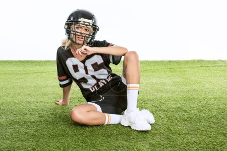 sporty young woman in american football uniform  isolated on white