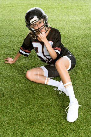 angry young woman in american football uniform sitting on grass and looking at camera