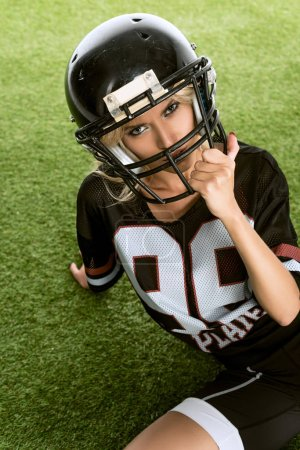 angry young woman in american football uniform sitting on grass